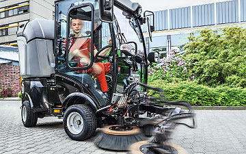 A cleaning service: A Dussmann operative sweeps the path with a ride-on machine