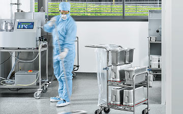 A cleaning service: A Dussmann operative works in clean-room overalls