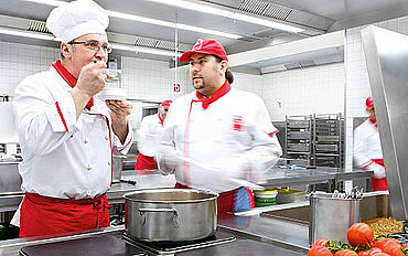 A facility service: 2 Dussmann cooks cook food on stoves
