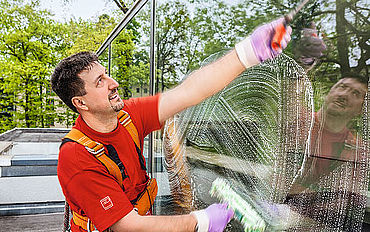 A facility service: a Dussmann operative cleans a large window